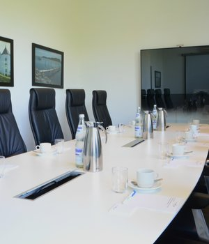 Conference room with long table and TV Hotel des Nordens